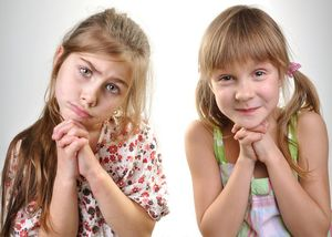 Portrait of two playful young girls asking for apologize or permission for something